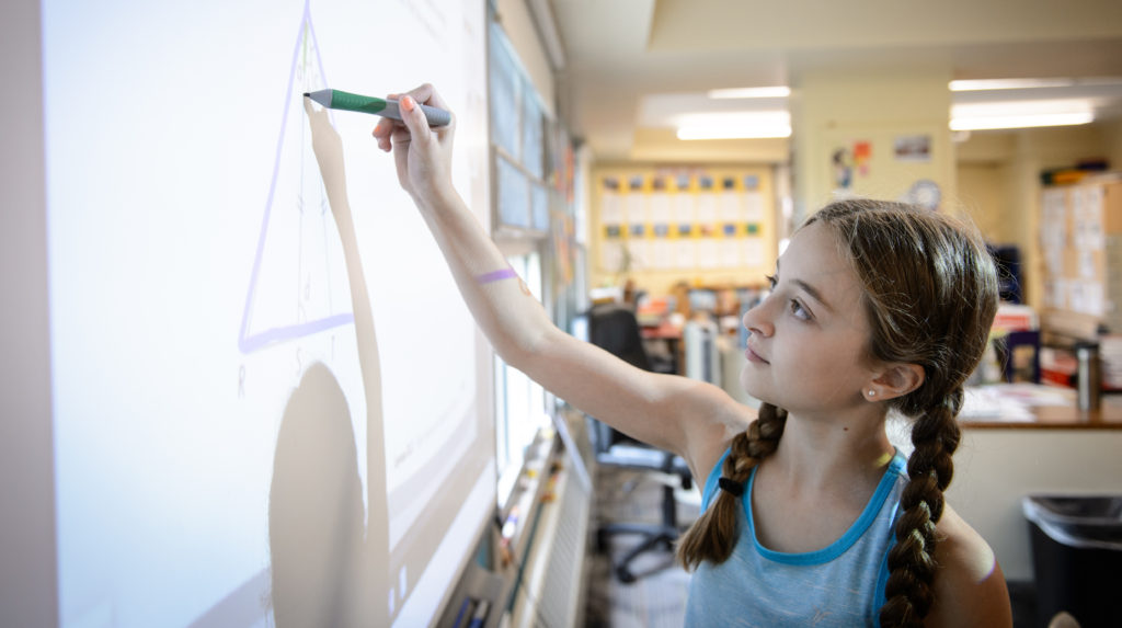 Girl elementary student at whiteboard drawing a triangle