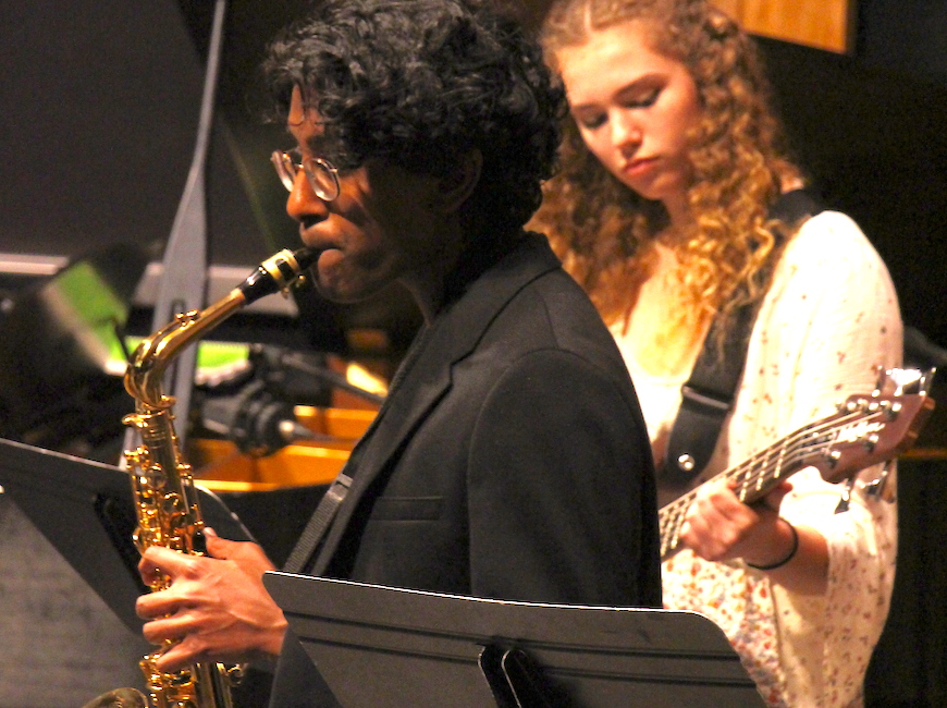 A boys plays saxophone and a girl behind him plays guitar at a performance.