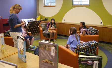 A librarian talks to four students sitting in comfy chairs in a brightly decorated reading room of the library.