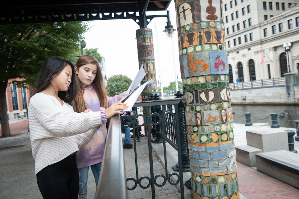 Two students look at their notes while standing near an art tile installation on a column near a bus stop in Providence.