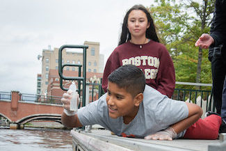 A boy pulls a water sample from a river in Providence while another student and teacher look on as part of the Cityside Program.