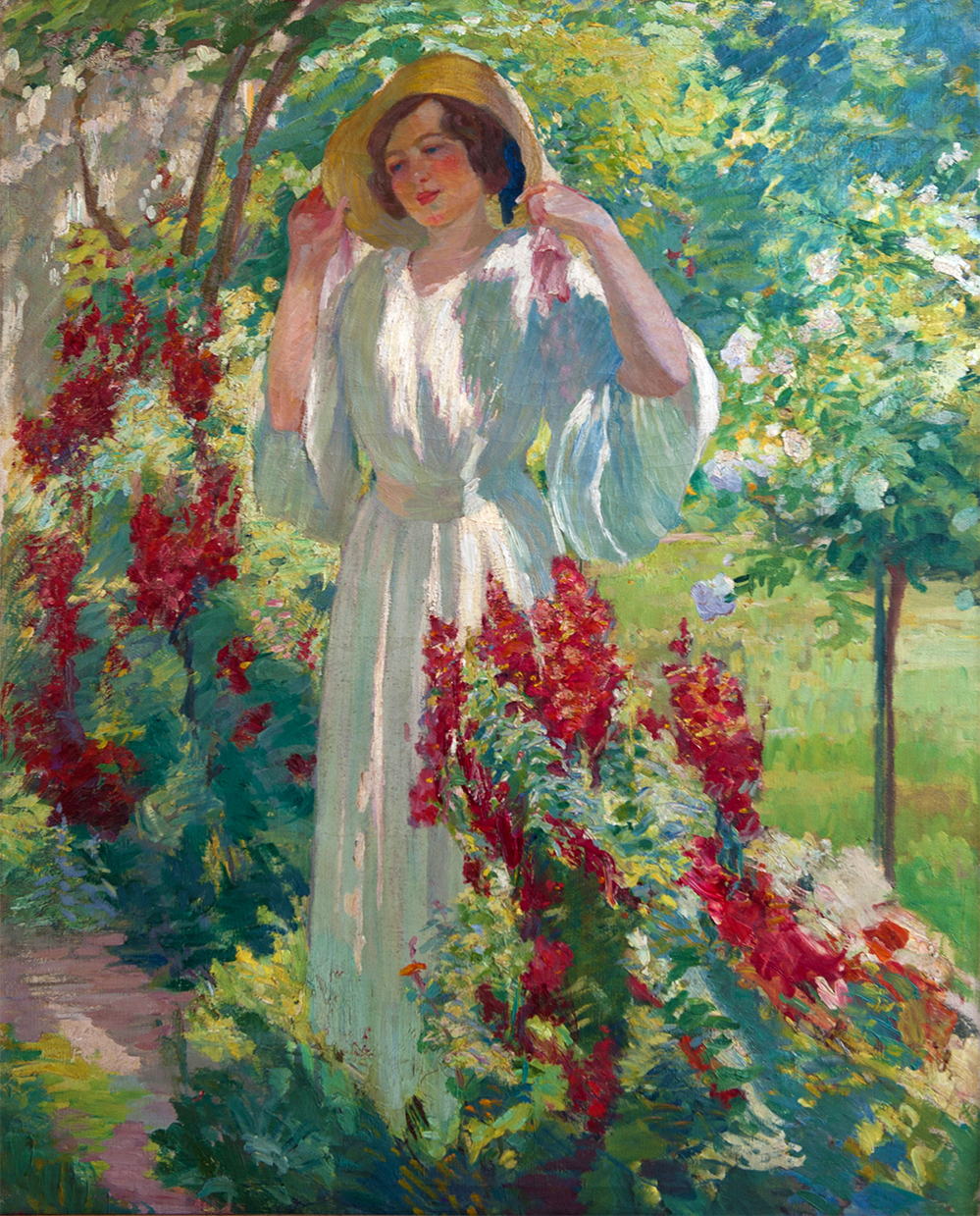 Portrait of a woman standing in a straw hat in a lush garden.