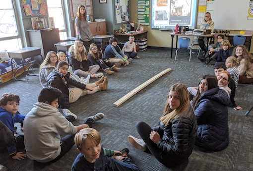 A large group of 8th-grade and 3rd-grade students sit on a classroom floor surrounding a wall stud they will decorate together for Habitat for Humanity.