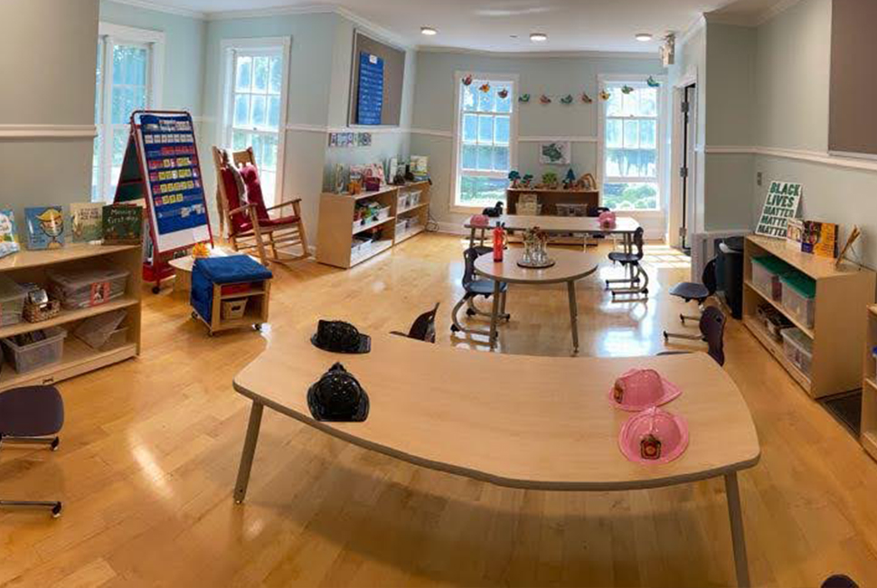 Long panoramic view of a new Nursery classroom with small tables and chairs, bright colorful flags, shelves, a rocking chair, and individual boxes of materials for each student.